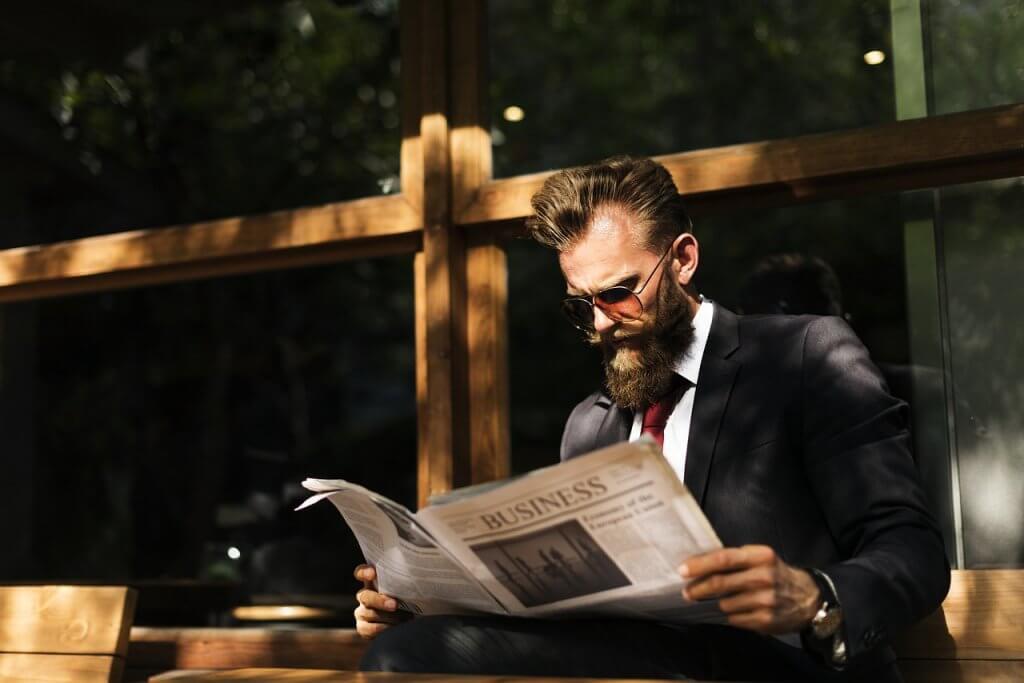 Businessman reading a newspaper about the best beard trimmer